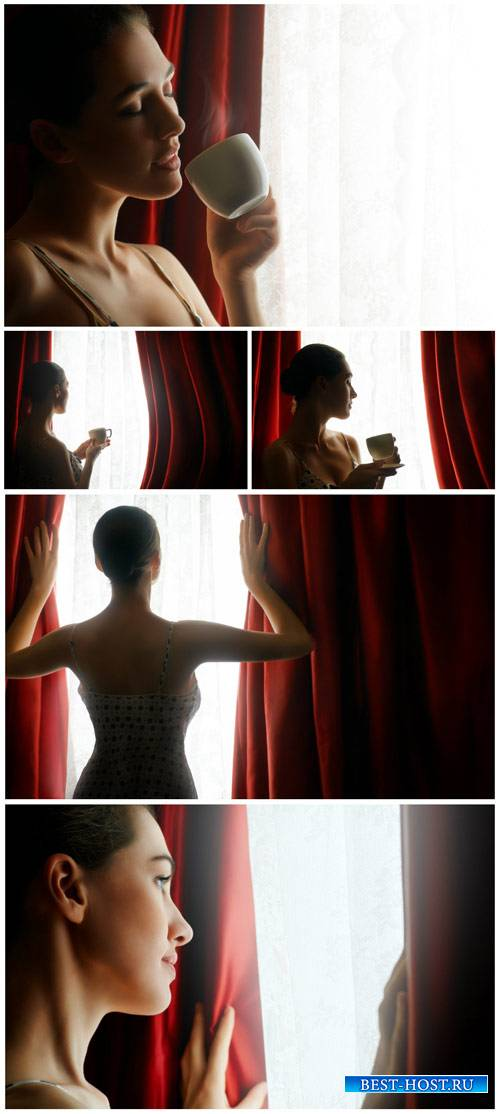 Woman with a cup of coffee by the window - Stock Photo