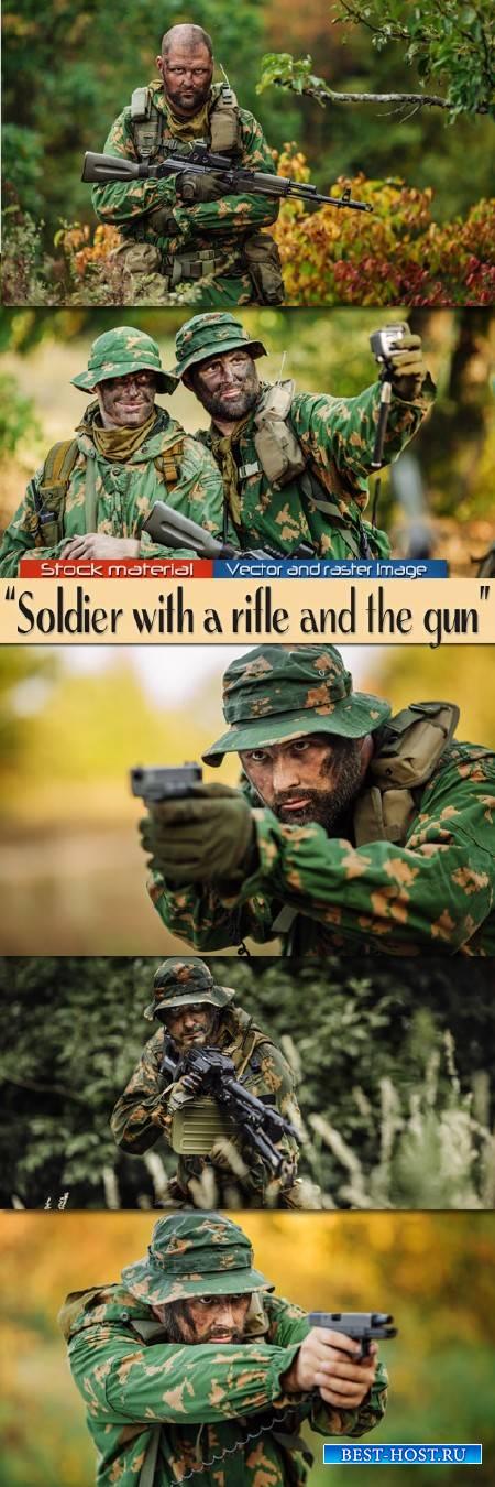 Солдат на поле боя с винтовкой и пистолетом