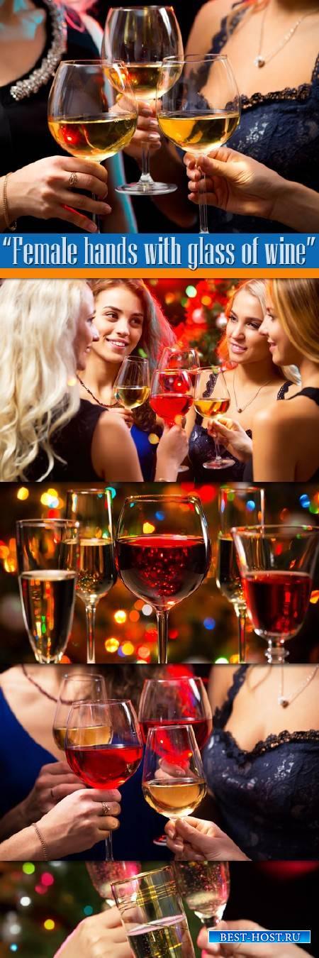 Женские руки с бокалом вина на празднике