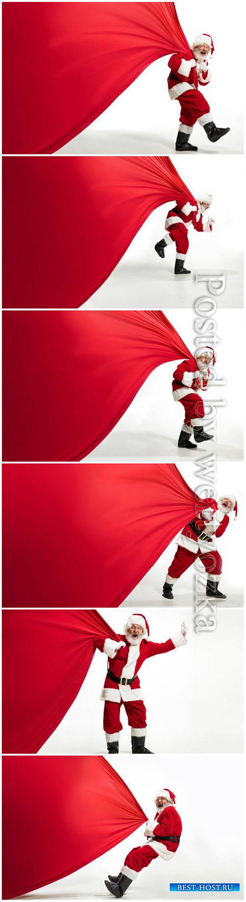 Santa Claus pulling huge bag full of christmas presents isolated on white b ...