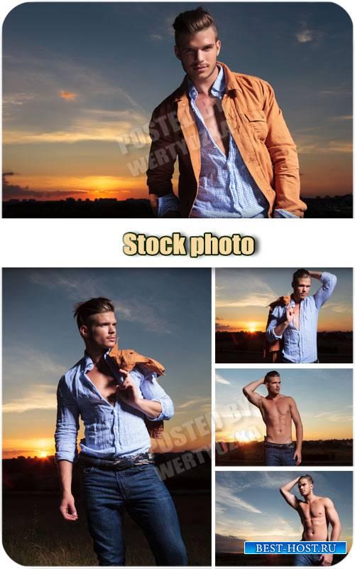 Молодой человек на фоне заката /  Young man at sunset - stock photo