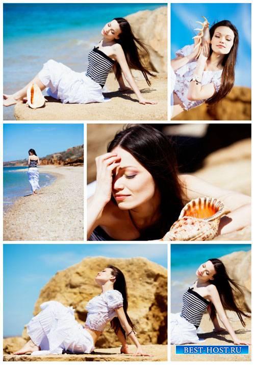 Красивая девушка с ракушкой на морском побережье