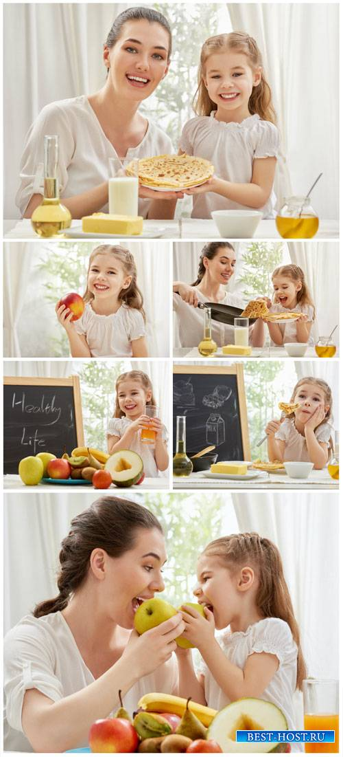 Woman with a little girl, fruit, pancakes - stock photos