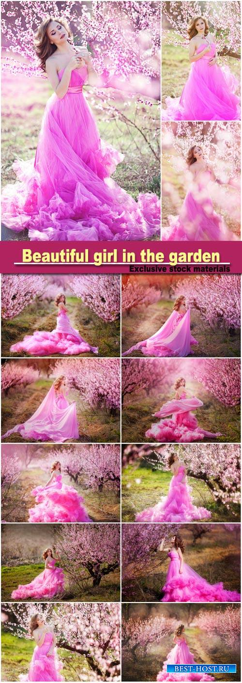 Adorable girl in blooming peach garden on sunny spring day