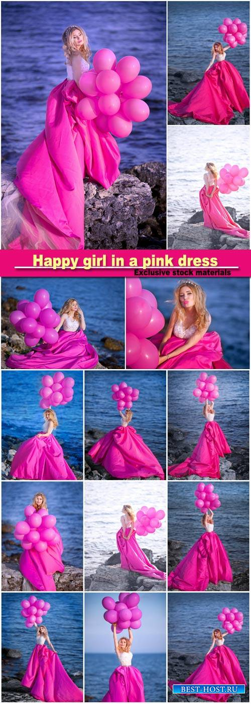 Happy girl in a pink dress with balloons is standing on the background of t ...