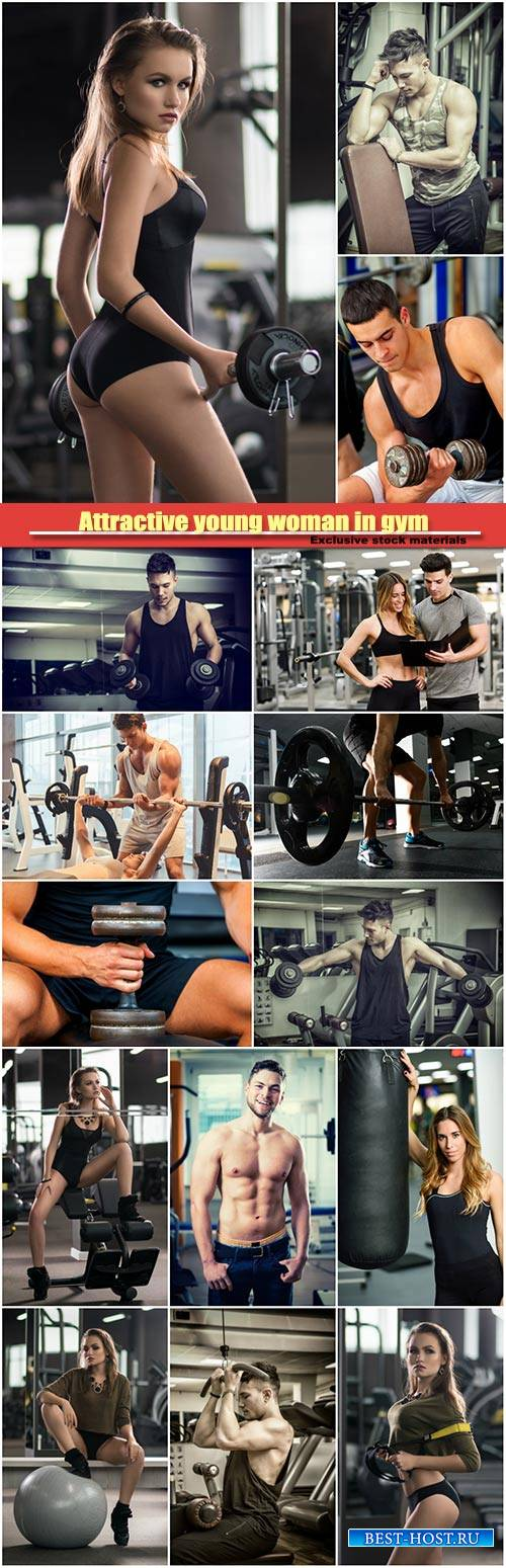 Attractive young woman is lifting weight in gym, handsome muscular trainer